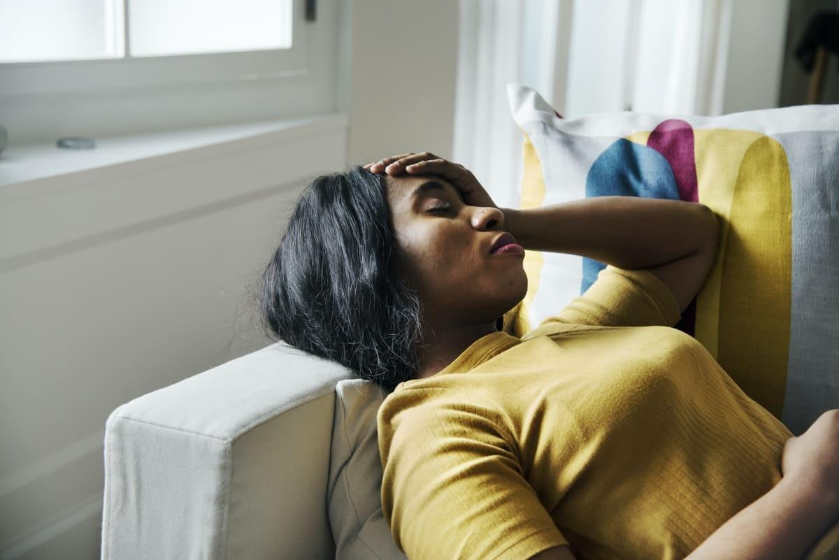 Titelbild: Frau mit Fibromyalgie und Depression liegt auf Couch