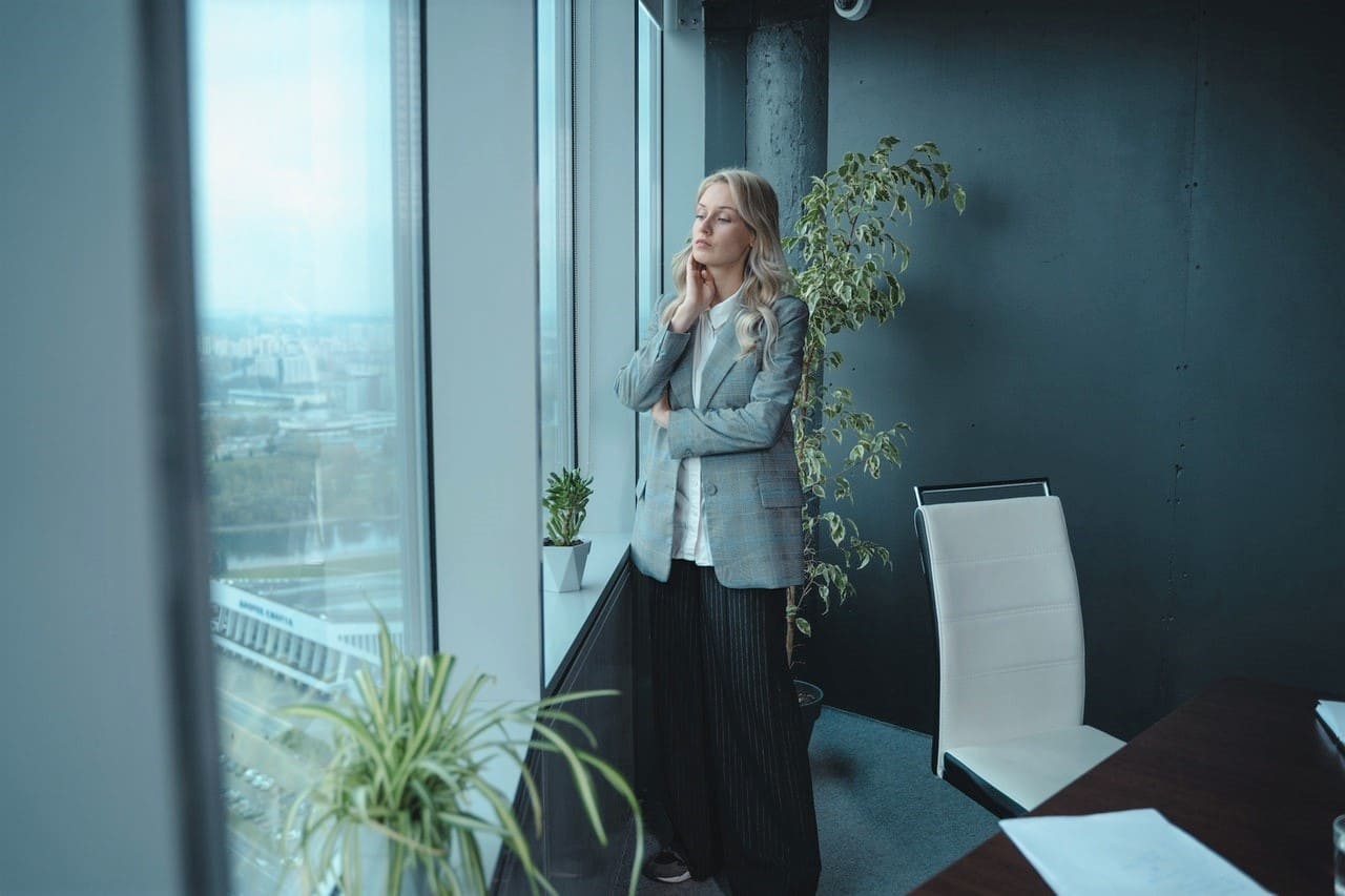 Titelbild: Chefin am Fenster mit Stress, Depression oder Stimmungstief