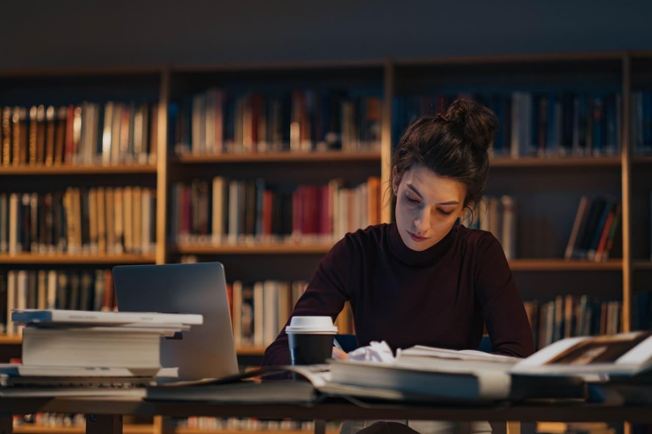 Titelbild: Frau in Bibliothek will Bunout im Studium vorbeugen