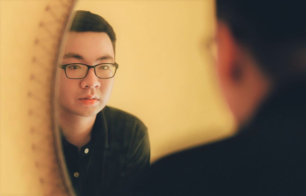 Titelbild: Junger Mann übt sich in Selbstakzeptanz vorm Spiegel
